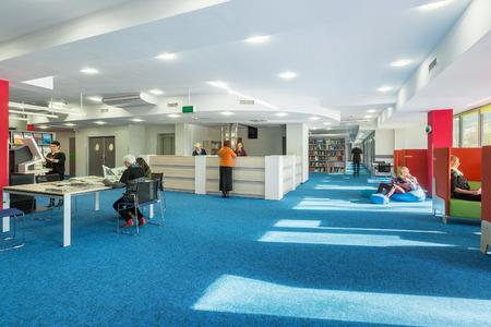 Biblioteca universitaria moderna e spaziosa con tappeto blu sul pavimento Archivio Fotografico