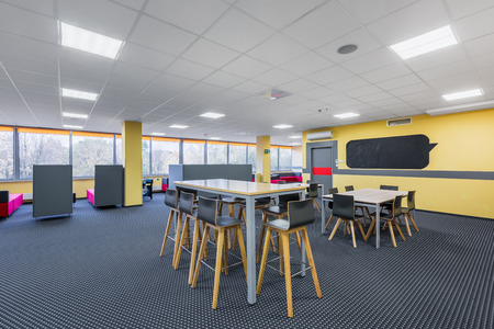 Bright library interior with high tables and stools