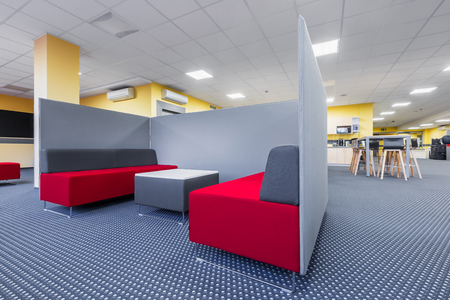Library lounge area with red sofa, table and grey partition