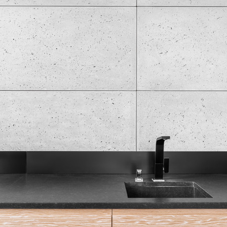 stone worktop: Modern kitchen with grey wall tiles, black worktop, sink and tap