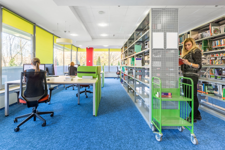Colorful library interior with computer workstation and modern shelving Banco de Imagens