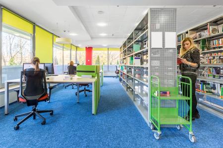 Colorido interior de la biblioteca con estación de trabajo informática y estantería moderna