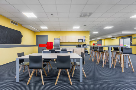 communal: Modern lunchroom interior with wooden tables and black chairs, kitchenette in background Stock Photo