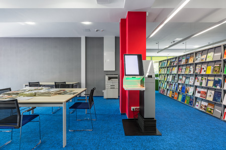 lend: Light library interior with big wooden table and black chairs, bookshelves and self-check lending books device