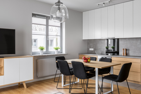 Minimalist, contemporary kitchen with dining room and tv screen