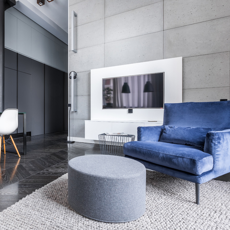 Living room with television, pouf table and armchair Banco de Imagens