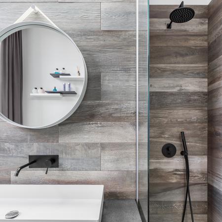ラウンド ミラー、木目調のタイルのシャワー付きのモダンなバスルーム