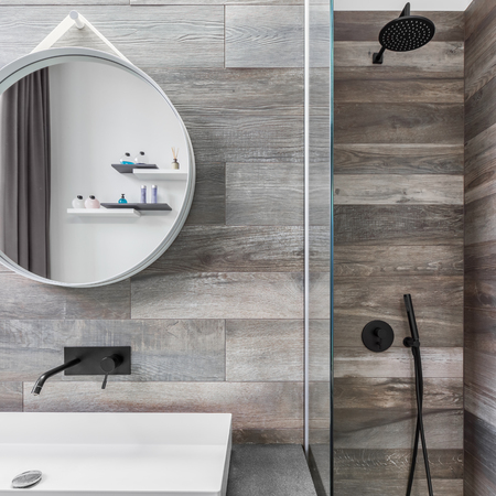 Modern bathroom with shower, round mirror and wood effect tiling Standard-Bild