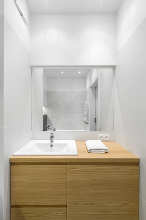 Luxury bathroom interior with big wooden commode and mirror
