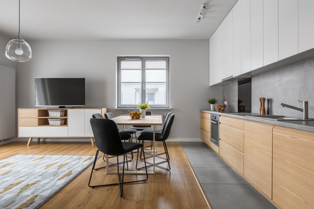 Modern apartment with open wood kitchen with table and long countertop