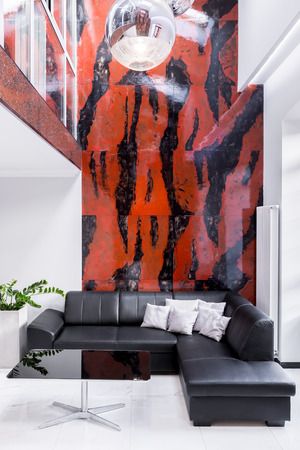 Luxury living room with large sofa, lamp, black and red marble wall