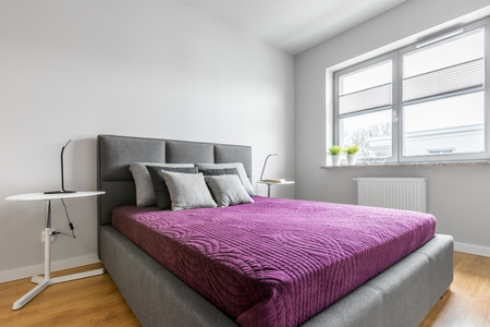 nightstands: Simple, white bedroom with grey upholstered bed, two nightstands and big window