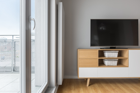 Tv living room with balcony, grey wall, wooden cabinet and floor panels Stock Photo