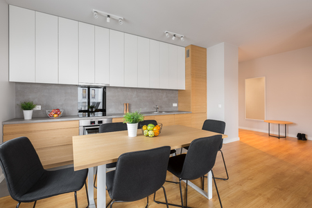 kitchen furniture: Open kitchen with table, chairs, white cupboards and wooden floor panels