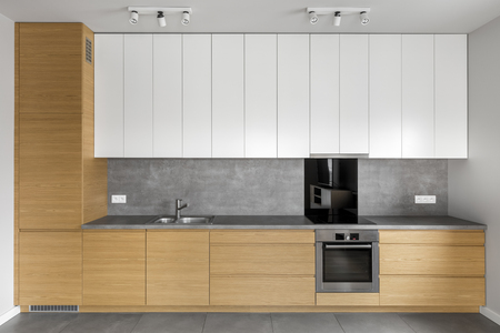 kitchen furniture: Grey kitchen with wooden cabinets, granite worktop and white cupboards Stock Photo