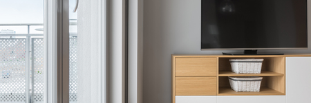luxury living room: Tv in living room with balcony, grey wall and wooden cabinet, panorama