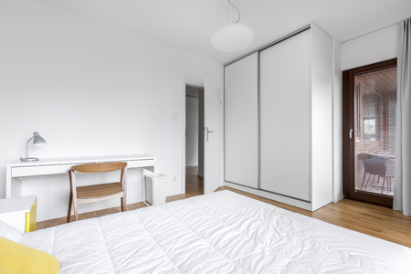 White bedroom with large wardrobe and work desk