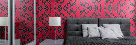 Cosy bedroom with big bed and patterned black and red wallpaper, panorama