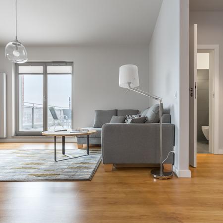 living room design: Modern living room with big window, next to hallway and bathroom doors open Stock Photo