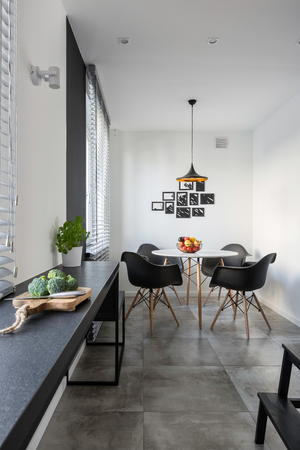 Modern, white kitchen with long, granite countertop, round table and chairs