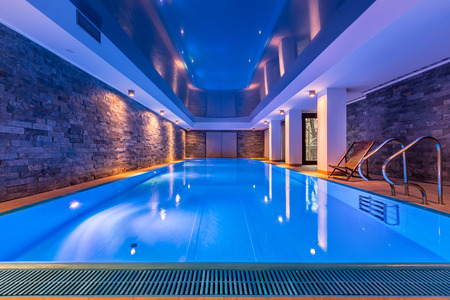 Luxurious villa swimming pool with brick walls, evening view