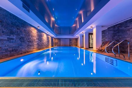 Luxe villazwembad met bakstenen muren, avondzicht