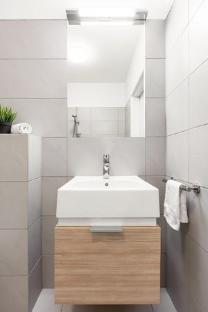 salle de bain beige avec lavabo moderne et miroir