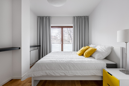 White bedroom with double bed, window, gray curtains, lamp and side table
