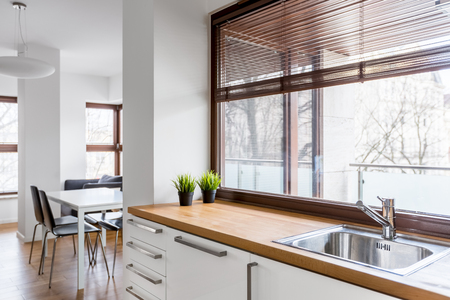 White kitchen with wooden countertop, silver sink and big window with blinds