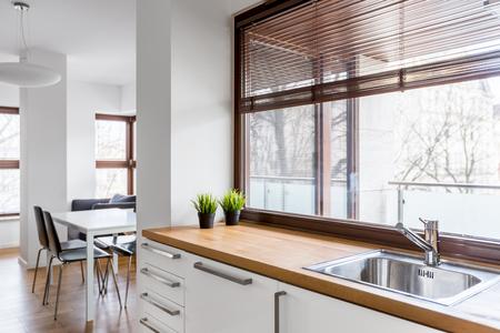 Witte keuken met houten aanrecht, zilvergootsteen en groot raam met blinds