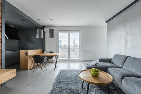 Gray living room with sofa, coffee table, balcony and kitchenette Standard-Bild