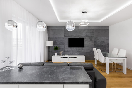 kitchen island: Modern, open plan apartment with concrete wall, lamps, tv, table and chairs Stock Photo