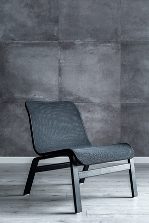 Elegant black chair in interior with concrete wall effect