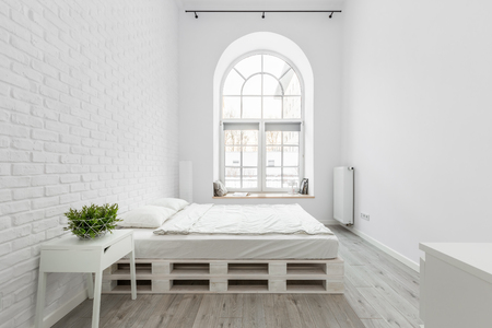 Loft bedroom with white brick wall, pallet bed and half circle window Standard-Bild