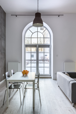 White loft interior with half circle window, dining table and chairs