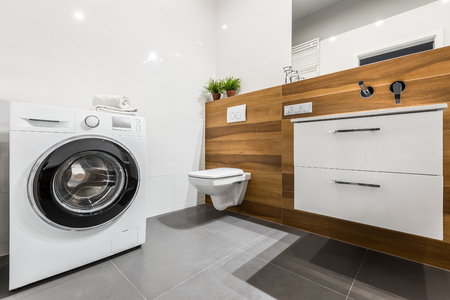 tiling: Wooden bathroom with white tiling, washer, cabinet and toilet Stock Photo