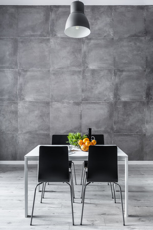 Dining room with concrete wall, white table and black chairs