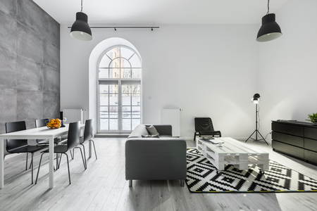 Modern loft interior with sofa, dining table with chairs, studio lamp and big window Stockfoto