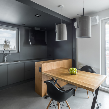 Dark gray kitchen with island, wooden table and black chairs 版權商用圖片