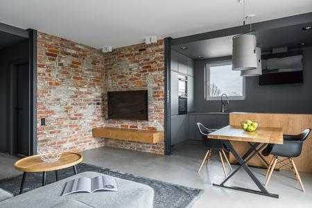 開いている、暗い灰色のキッチン付きのモダンなリビング ルーム