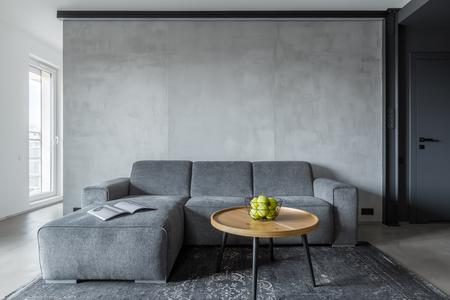 Sala de estar con sofá gris y mesa de centro redonda