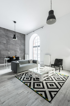 Loft apartment with open living room with sofa and pallet table
