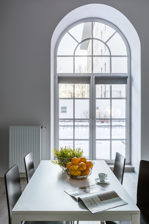 White dining room with half circle window, table and chairs Standard-Bild