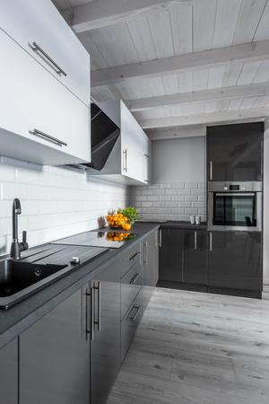 木製の天井と、モダンな黒と白のキッチン
