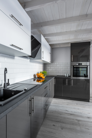Modern, black and white kitchen with wooden ceiling