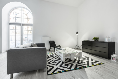 White living room with gray sofa, pallet table and black cabinet Stockfoto