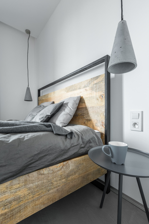 White bedroom with wooden bed, side table and modern concrete lamps Standard-Bild