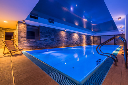 Luxurious swimming pool with brick wall and deck chair