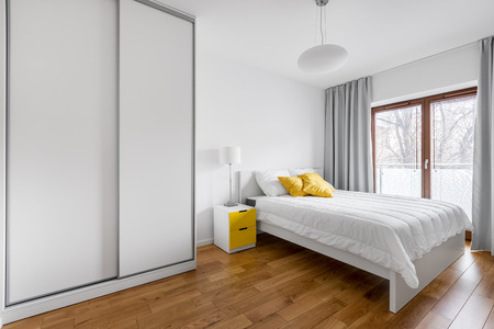 Modern bedroom with white wardrobe and double bed