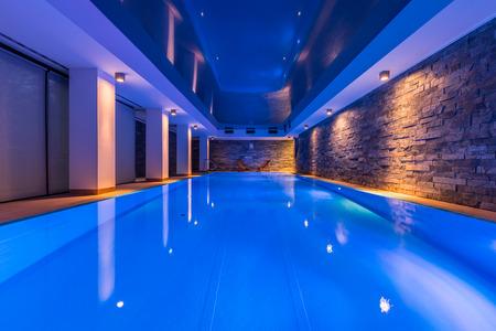 Schwimmbad mit dekorativen LED-Lichtern und Backsteinmauer Standard-Bild